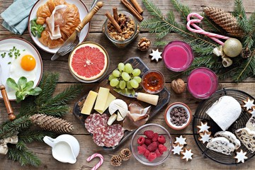 Christmas brunch or breakfast table. Festive brunch set, meal variety with fried egg, appetizers platter, croissant, granola, smoothy and traditional sweets . Overhead view