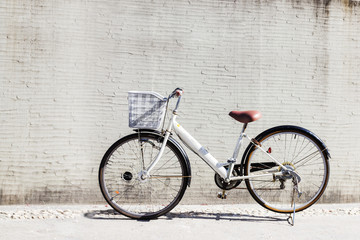 bicycle with basket in front of the white wall
