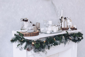 White decorated fireplace for Christmas. Wooden logs and white candles with glass jars