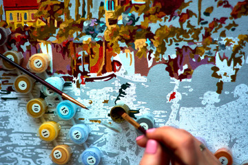 the girl draws a brush paints a picture of the numbers
