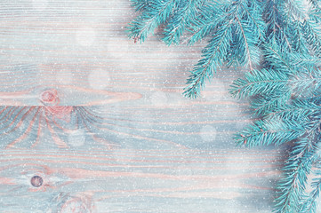 New Year and Christmas background. Blue fir tree branches with snowflakes on the light wooden background