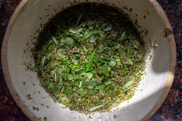 bowl of fresh sage and rosemary herbs in bowl in sun