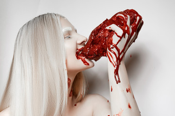 A young girl soiled in blood bites fresh meat.