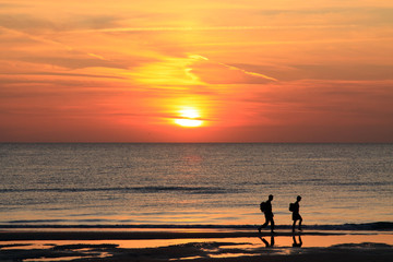 Golden sunset and people on the North Sea beach in Bloemendaal, The Netherlands.