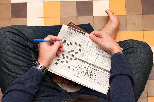 young man doing crossword puzzle in newspaper