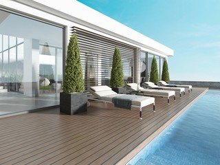 Terrace by the pool with sun loungers near the modern house.