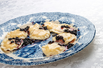 Vareniki with ricotta cheese and elderberries on a decorative plate