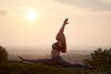 Silhouette of attractive slender long-haired barefooted young woman in summer training outfit doing gymnastic yoga exercises outdoors on grassy hill under bright pink misty sky at sunset or sunrise.