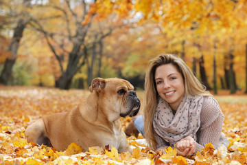 Cute continental bulldog lying  in autumn with its owner  on the ground