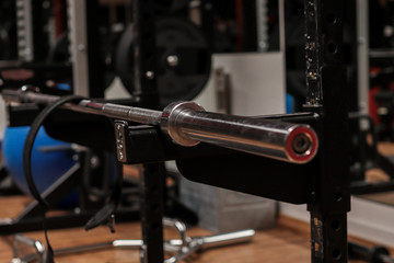 A gym with a lifting dumbbell bar and a lifting belt. sports, lifting equipment;