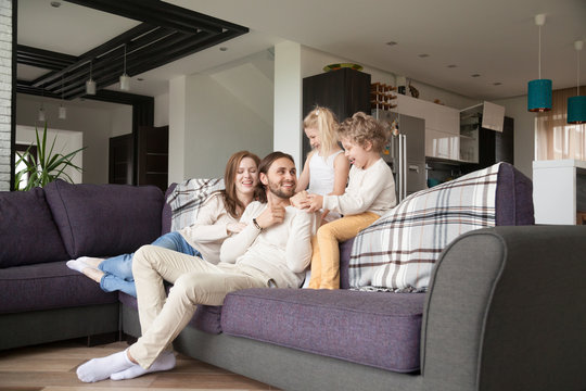 Young attractive married couple with little preschool children sitting on couch in living room at new modern wealthy house. Happy playful parents and joyful kids spending free time or weekend together