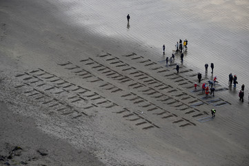 Pictures of soldiers are etched in the sand on Armistice day to commemorate those killed in World War One, part of Danny Boyle's Pages of The Sea celebrations, on Downhill Beach in Coleraine