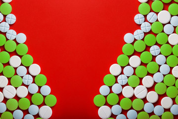 The concept of medicine. Medical green pills. On a red background. View from above .