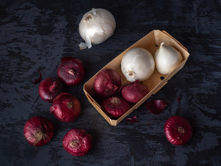 A wooden box with red and white onions lies on a dark background with a virgin.