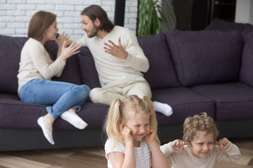 Family with little preschool children at home. Wife and husband sitting on couch and quarreling, screaming. Sad daughter and son sitting on floor suffer and closing ears with hands not to hear parents