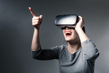 Young woman using a virtual reality headset on a gray background