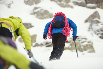 Mountaineers climb the snow-covered mountain slope in bad weather.