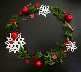 Christmas wreath frame on dark wooden background. Minimalist trend design. Space for text.