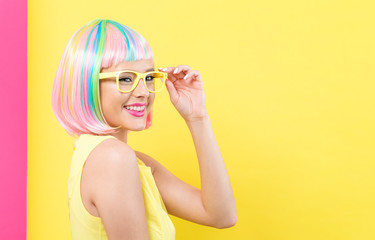 Young woman in a colorful wig with sunglasses on a split yellow and pink background