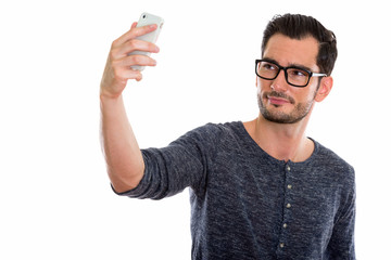 Studio shot of young handsome man taking selfie picture with mob