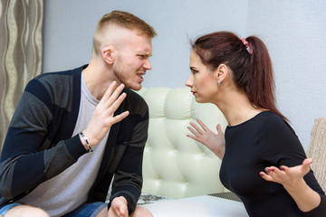 The concept of family conflict, problems, relationships of young disgruntled husband and wife in a room on the sofa.