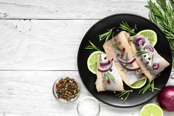 herring fillet with pepper, rosemary, onion and lemon on black plate on white background. top view with copy space