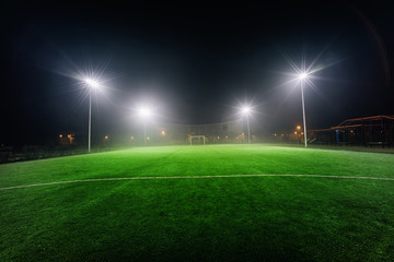 Illuminated football playground with green grass, modern football goal net and lens flares on background.