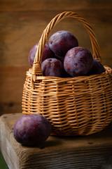 Ripe blue plums in wicker basket
