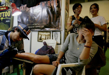A woman gets a tattoo during the Art Tattoo Convention in La Paz
