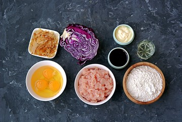 Ingredients for okonomiyaki, national Japanese dish: red cabbage, eggs, flour, mayonnaise, teriyaki sauce, sliced chicken fillet, tuna flakes, frying oil.