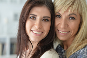 Portrait of middle aged woman with daughter hugging