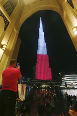 A man takes a pictures of Burj Khalifa, the world's tallest building, lit up in the colours of the Polish flag to mark the 100th anniversary of regaining independence in Dubai
