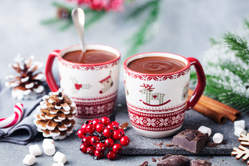 Hot chocolate with marshmallows in Christmas mugs on grey background. Copy space. Close up.
