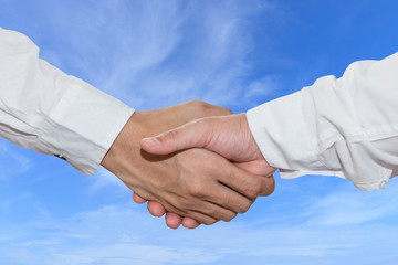 Business people shake hand in front of blue sky background