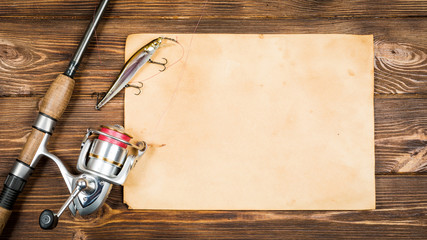 Fishing gear - fishing, fishing, hooks and baits, an old sheet of paper on a wooden background. Toned image