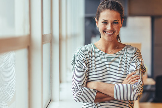 Smiling businesswoman standing with crossed arms