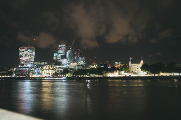Skyline of London with the antique Tower of London and the modern buildings of the business district along the river Thames with lots of cranes in the background at night