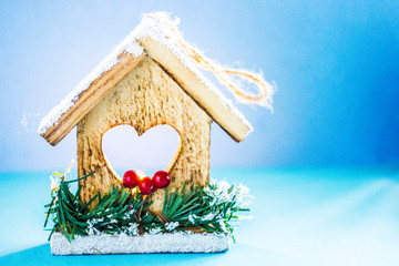 Christmas background - a decorative wooden house with a heart window and a roof in the snow