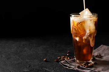 tall glass cold brew coffee with ice and milk on black or dark background