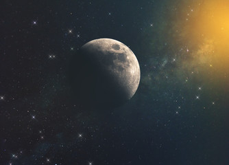 the moon against the milky way and the rays of the sun in the infinite space of the universe