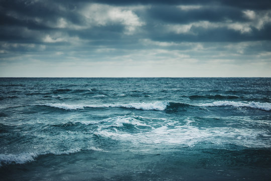 Water waves on cloudy sky background