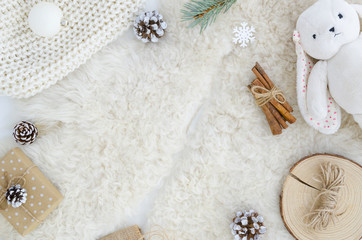 Flat lay fur background with pine cone fir branch,rope,rabbit toy, cinnamon.Top view copy space mockup. Cosy, soft ,minimal. Christmas,new year, birthday, xmas