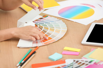 Designer with paint color palette samples at table, closeup