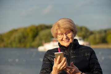 Senior woman walk in the park and look at smartphone