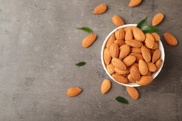Tasty organic almond nuts in bowl and space for text on table, top view