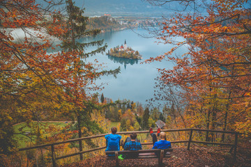 Foto op Aluminium Japan Young boys sitting on bench and looking at Bled Lake, Island,Church And Castle, Slovenia, Europe