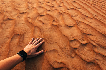 Man hand is touching sand in a desert at sunset