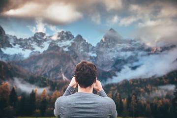 Man looking at mountains in autumn time. Julian Alps in background. Slovenia, Kranjska Gora