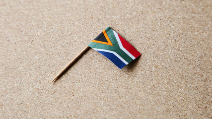 A small South African flag isolated on a wooden background. This image can be used to represent Heritage day.