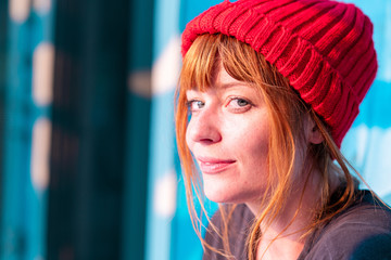 Cute ginger girl with blue eyes and red beanie on a blue wall at sunset